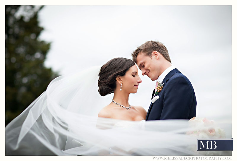 bride and groom smiling with long flowing veil